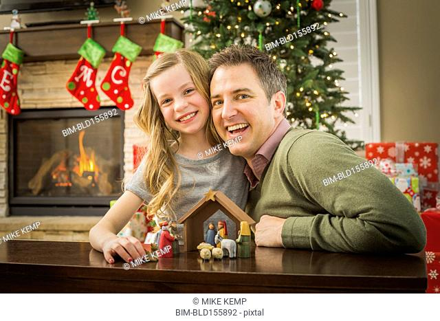 Caucasian father and daughter arranging nativity at Christmas