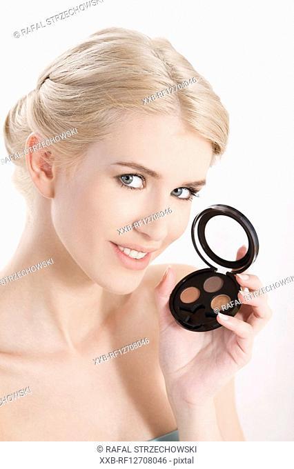 woman holding eye shadows