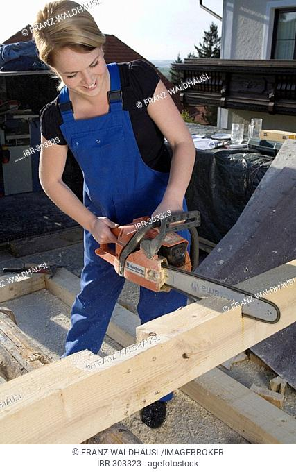 Young woman works with a chain saw