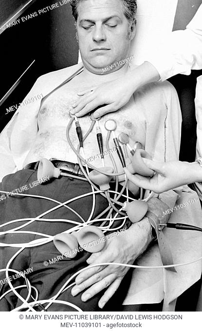 Biomedical centre, London -- a woman attaches sensors to a patient