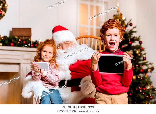 portrait of santa claus in rolling chair and children with digital devices