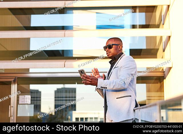 African American businessman with mobile phone on a summer afternoon