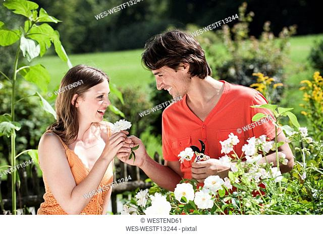 Germany, Bavaria, Couple in the garden, man giving woman flower, smiling, portrait