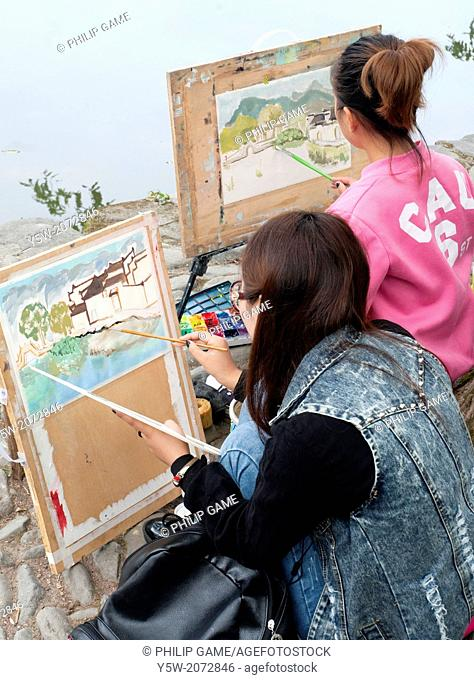 Chinese art students working on watercolour painting in Hongcun heritage village in Huizhou region, Anhui