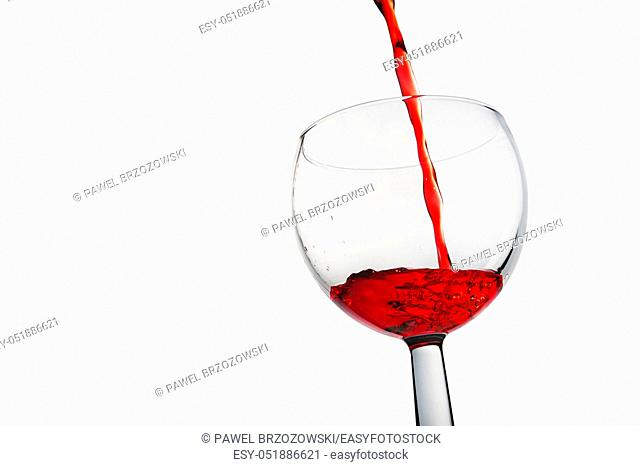 Red wine is pouring into a glass