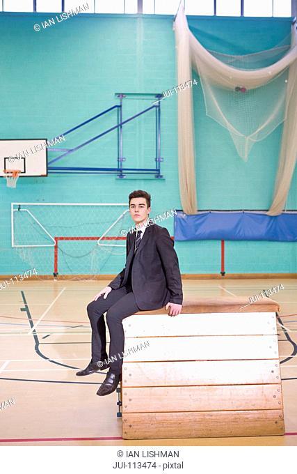 Portrait confident high school student wearing suit in gym