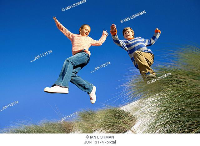 Exuberant brother and sister jumping for joy over sand dune beach grass