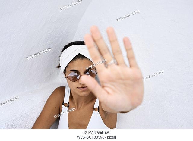 Young woman wearing white bikini top raising her hand