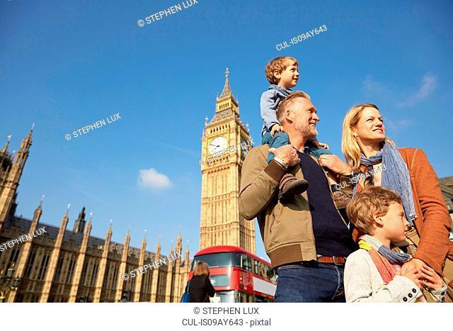 Family in front of big ben looking away