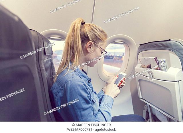 Blond young woman in airplane using smartphone