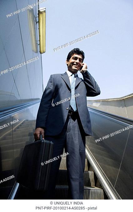 Businessman talking on a mobile phone on an escalator, Gurgaon, Haryana, India