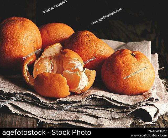heap of unpeeled round ripe orange mandarin on a gray linen napkin, wooden table, low key