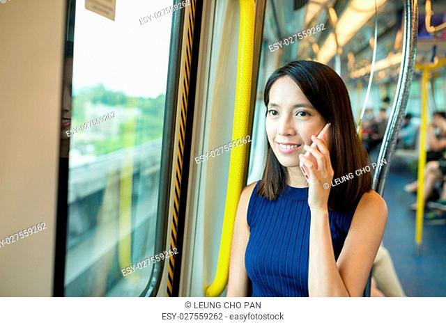 Woman talk to mobile phone in train