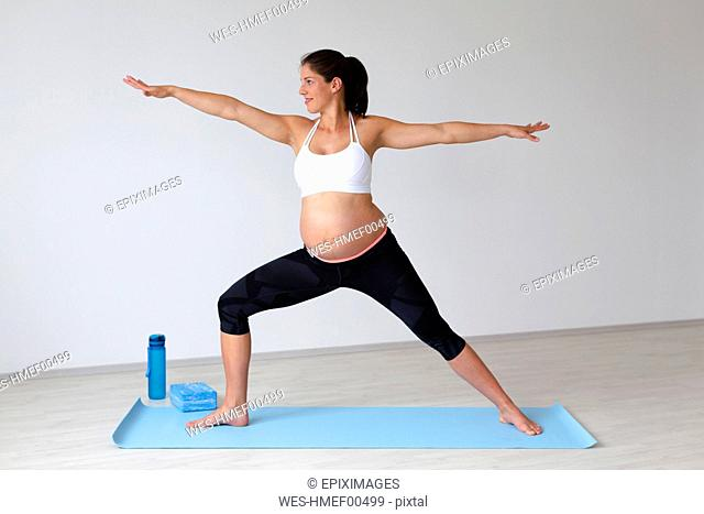 Young pregnant woman practicing yoga, warrior pose