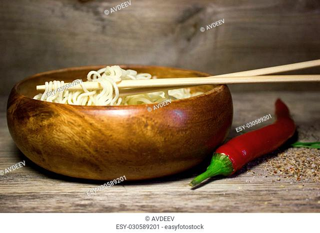 Instant noodles in a wooden bowl with chopsticks. Wooden background and red pepper