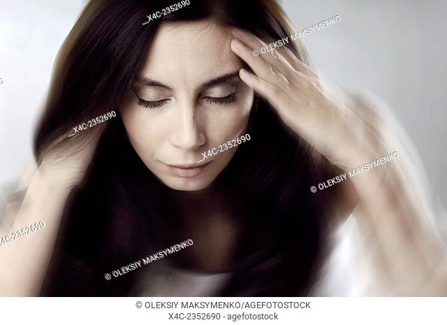 Artistic conceptual portrait of a young woman with her head spinning, headache, stress concept