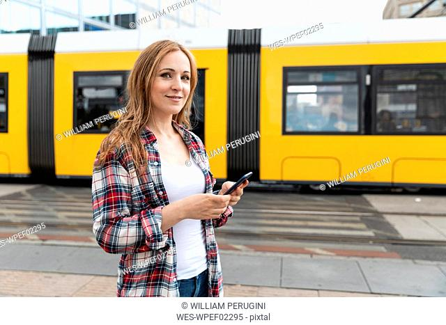 Portrait of a smiling woman in the city with a tram in the background, Berlin, Germany