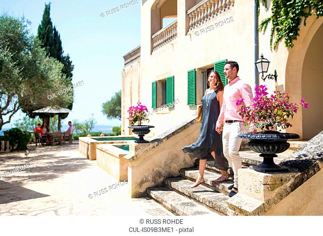 Couple moving down stairway at boutique hotel, Majorca, Spain