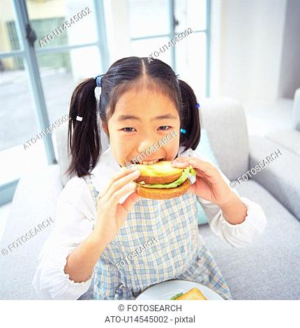 Girl eating a sandwich While sitting on a sofa, looking at camera, Smiling, High Angle View, Differential Focus