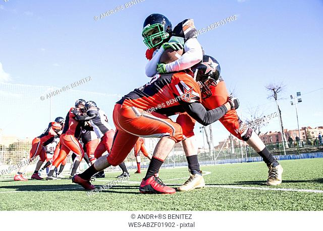 American football player being tackled by opponent player during a match