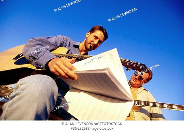 Adults musicians practicing guitar