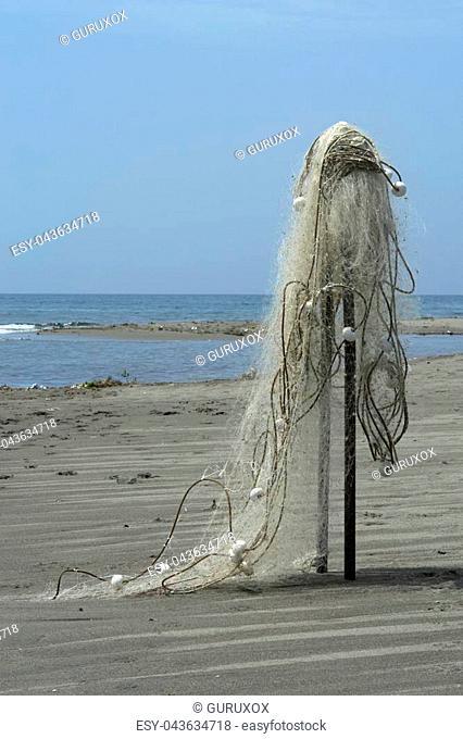 Fishing net with white buoys on the sandy beach. Fishing equipment