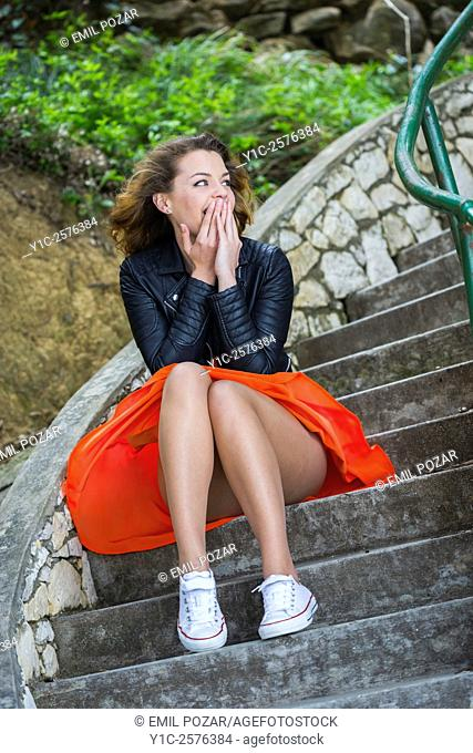 Pretty teen girl in Red skirt and sneakers is excited looking away