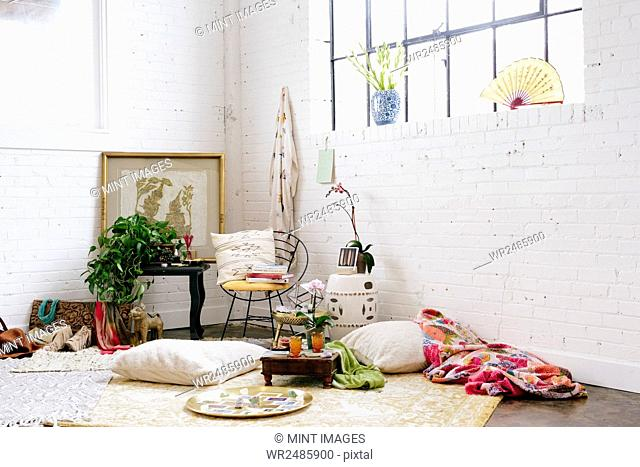 A light airy room with whitewashed walls. Cushions and possessions scattered across the floor