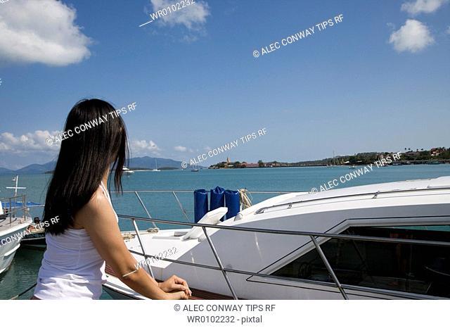 Thailand, Koh Samui. Woman at harbour looking toward sea