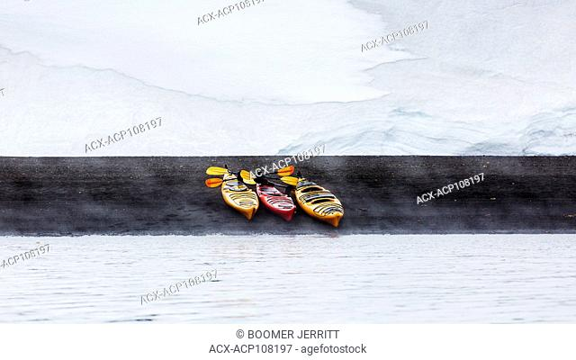 A white snowfield in the background contrasts with three Kayaks pulled up onto the black volcanic sands of Whaler's Bay, Deception Island