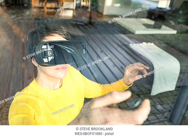 Portrait of woman behind windowpane using Virtual Reality Glasses at home