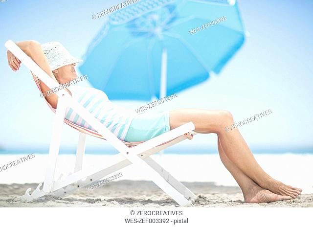 Woman on beach relaxing on a beach chair