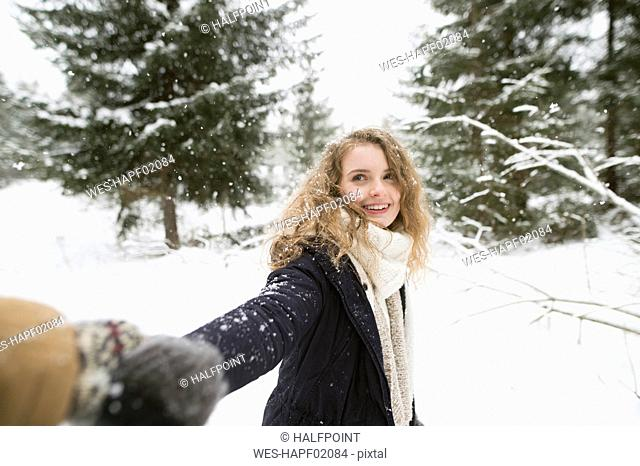 Portrait of happy young woman holding hand in winter forest
