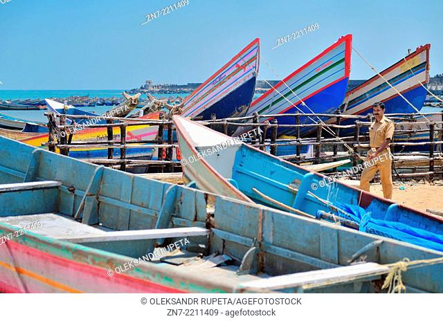 Worker walking among fishing boats at the Vizhinjam fishing harbour, Vizhinjam, India