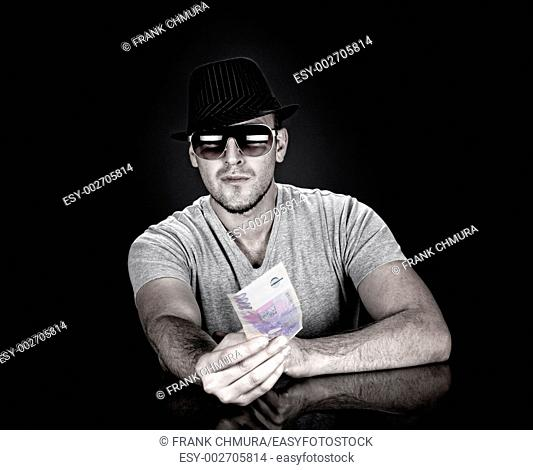 man in hat and sunglasses holding out one thousand czech krona bank note