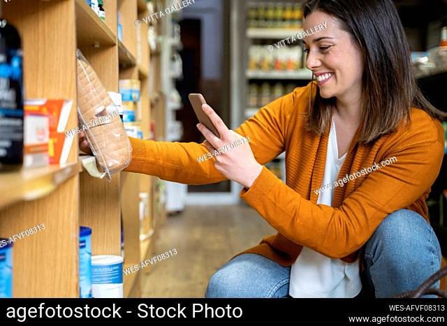 Happy young woman photographing package in grocery store