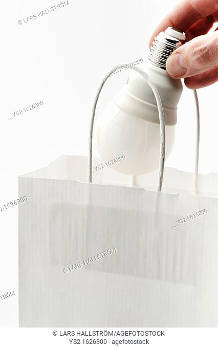Hand placing energy efficient lightbulb in paper bag