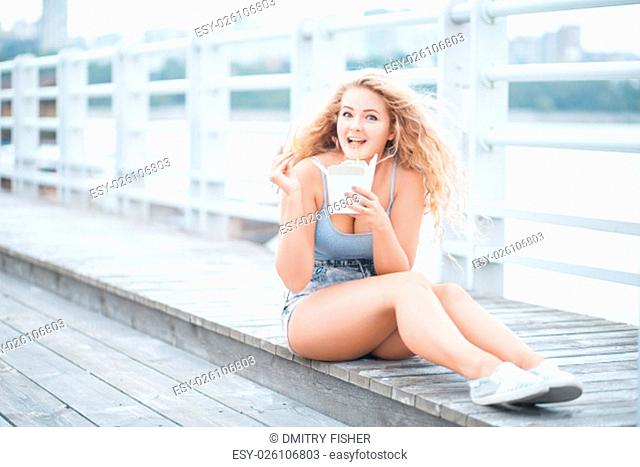 Happy young woman with long curly hair, sitting on the wooden floor, holding a lunch box and eating up noodles from Chinese take-out with chopsticks