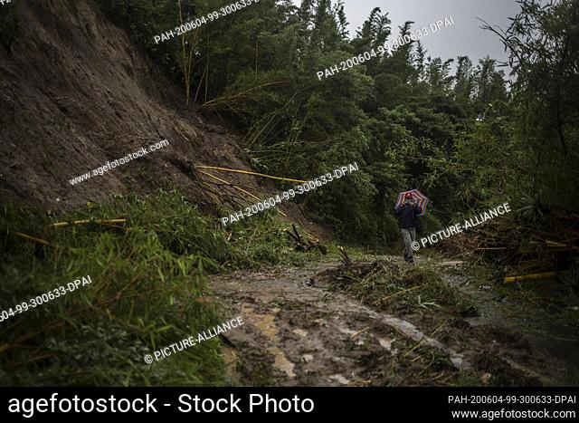 03 June 2020, El Salvador, Santo Tomás: A man walks near the landslide caused by the rains in the municipality of Panchimalco