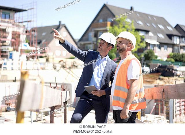 Man in suit talking to construction worker on construction site