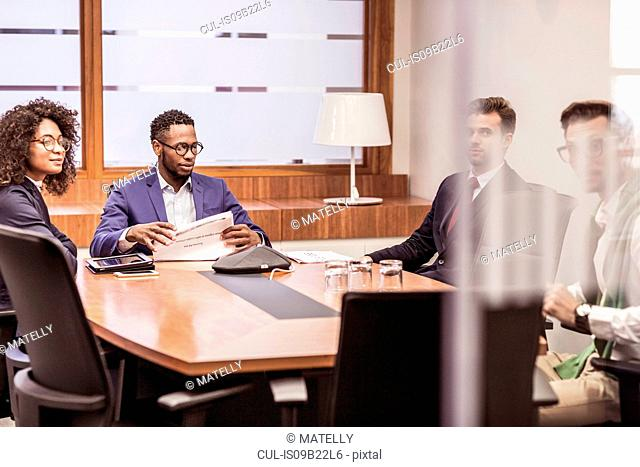 Businesswoman and men having discussion at boardroom table meeting