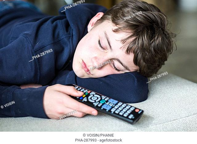 Teenage boy sleeping on a couch, holding a remote control