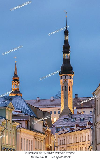Tallinn, Estonia, Europe. Old Medieval Tower Of City Hall On Blue Sky Background. Ancient Tower Of Town Hall In Evening Or Night Illuminations