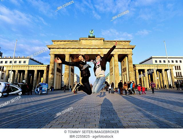 Jumping for joy, two girls jumping in the air in front of the Brandenburg Gate, Berlin, Germany, Europe