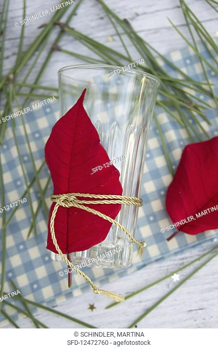 A glass decorated with poinsettias and pine needles