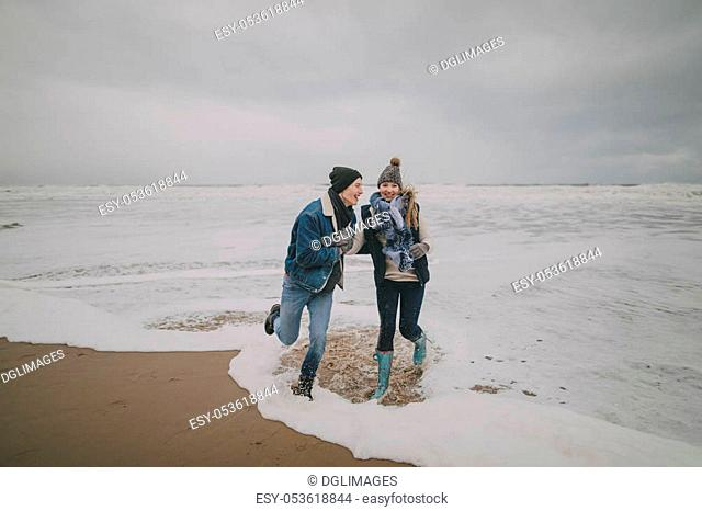 A young couple laugh and paddle in the sea on a winter beach
