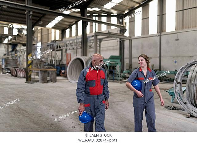 Male and female worker walking and talking in factory
