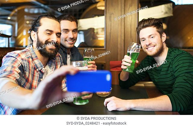 friends taking selfie with green beer at pub