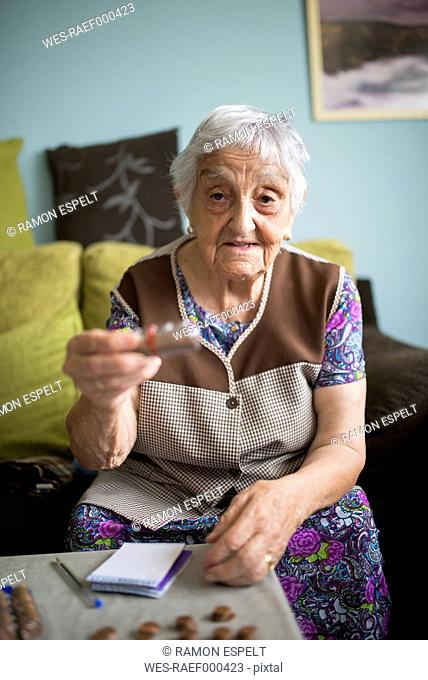 Portrait of senior woman sitting on couch at home showing a package of coins