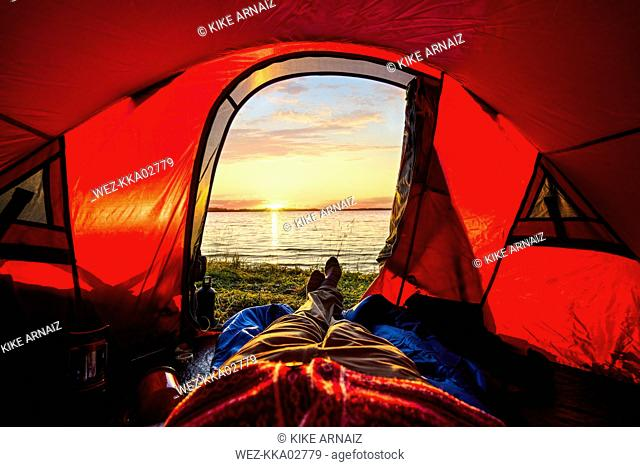 Man camping in Estonia, watching sunset lying in tent
